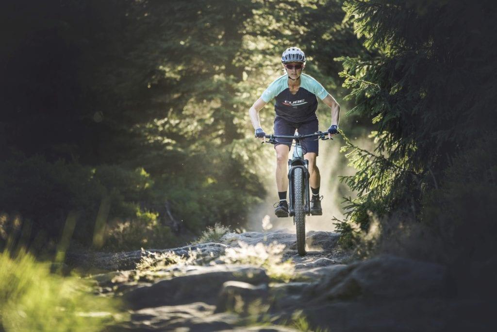 A woman riding a Cube bike on a trail